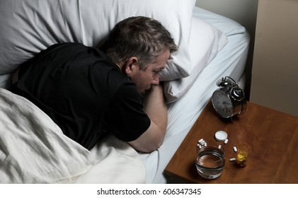 Mature man staring at alarm clock while trying to fall asleep. Insomnia concept.
