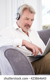 Mature Man Streams Music From Laptop To Wireless Headphones