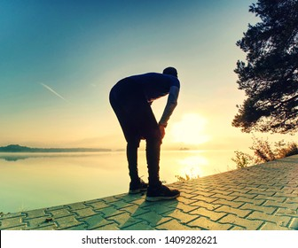 Mature man  stretches muscles while resting after jogging. Happy sports man feeling refreshed after exercise.