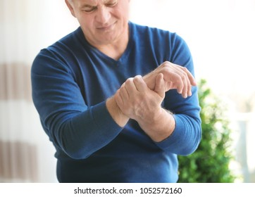 Mature man suffering from hand pain at home