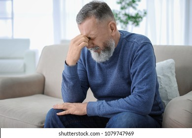 Mature man suffering from headache at home