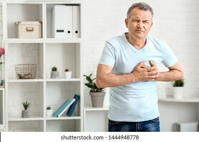 Mature man suffering from heart attack at home