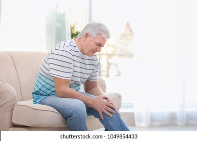 Mature man suffering from knee pain at home
