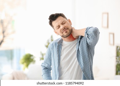 Mature man suffering from neck pain at home
