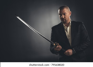 mature man in suit with katana sword on black