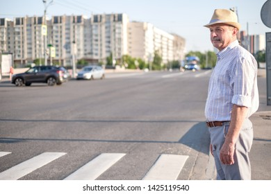 Mature man in summer hat waiting to cross street on sunny day.