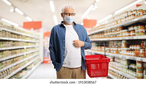 Mature man in a supermarket carrying a shopping basket and wearing anti virus face mask