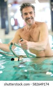 Mature man in swimming-pool doing aquabike exercises