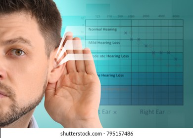Mature man with symptom of hearing loss on blurred background