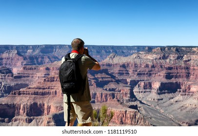 Mature man taking photos of the Grand Canyon during summer season