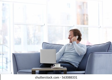 Mature man talking by mobile phone while sitting on sofa at home