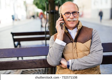 Mature man talking on phone while sitting on the bench