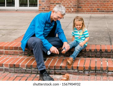 Mature man tickling foot of toddler girl while cleaning shoes – Gelsenkirchen, Germany