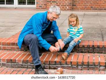 Mature man tickling foot of toddler girl while cleaning shoes – Gelsenkirchen, NRW, Germany
