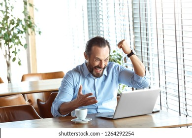 Mature man trader sitting at table at cafe at daytime with cup of coffee looking at laptop screen hand in fist up success achieved smiling happy.