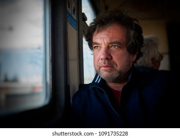 Mature man in a train by the window