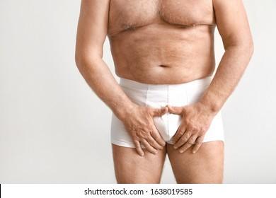 Mature man with urologic disease on light background