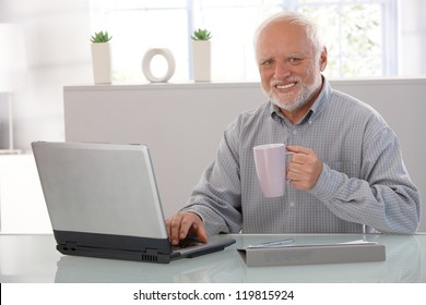 Mature man using computer, drinking tea, looking at camera, smiling.