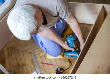 Mature man using electric screwdriver while making bookcase or shelf unit