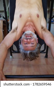 Mature man using inversion table at  gym