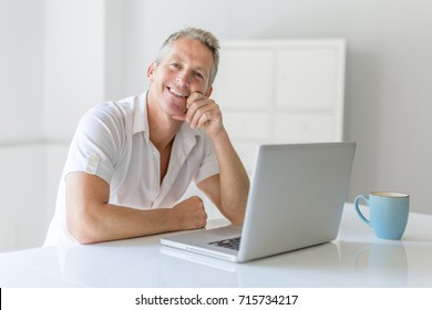 Mature Man Using Laptop On Desk At Home