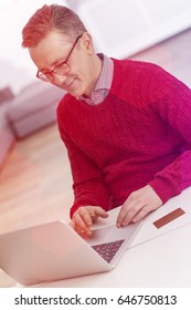 Mature man using laptop at table in house