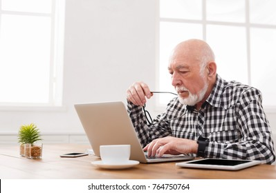 Mature man using laptop and writing in notepad at home desk. Education, recipe concept