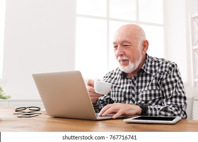 Mature man using laptop and writing in notepad at home desk. Education, recipe concept, copy space