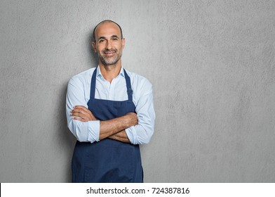 Mature man wearing blue apron isolated on grey background with copy space. Successful senior man wearing apron with crossed arms on grey wall. Satisfied owner and small business concept.