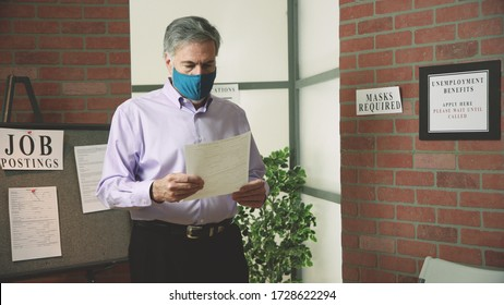 A mature man wearing a mask because of COVID19 mandates in an unemployment office looking at the application for benefits he is to complete.