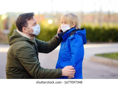 Mature man wearing a protective mask puts a face mask on a his son in airport, supermarket or other public place. Safety during COVID-19 outbreak. Epidemic of virus covid.