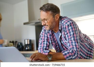 Mature man websurfing with laptop in home kitchen
