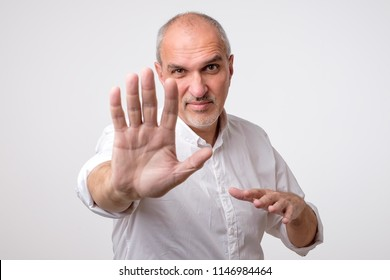 Mature man in white shirt showing sign stop with hand. Deny to do something