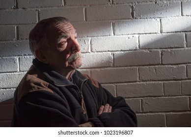Mature man with a white wall background looking into a beam of light