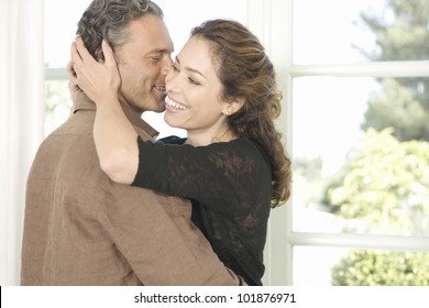 Mature man and woman hugging and whispering in each other's ear.