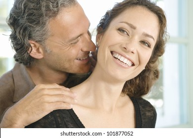 Mature man and woman hugging and whispering in each other's ear at home.