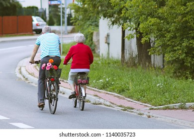 Mature man and woman rides a bicycle among the greens. A healthy and active part of life. Ecological transport for the population. Free time for retirement. Movement in space. Sports for the elder