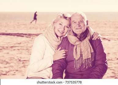 Mature man and woman sitting comfortably on bench by sea