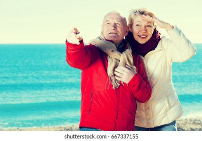 Mature man and woman walking by sea and pointing upwards