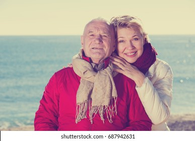Mature man and woman walking by sea on sunny day