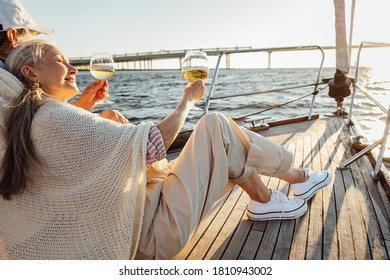 Mature man and woman wrapped in plaid on yacht deck and drinking wine. Senior couple holding glasses of wine on sailbot.