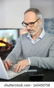 Mature man working from home with laptop computer