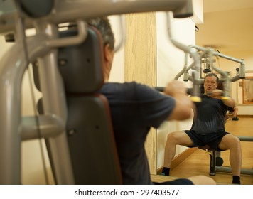 Mature man working out on shoulder press machine. Regular physical activity for keeping fit and healthy. Shot in motion and mirror reflection