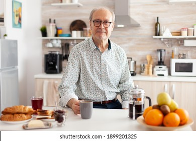 Mature man with wrinkles looking at camera in modern kitchen enjoying a cup of coffee. Portrait of relaxed elderly senior person in the morning, drinking fresh warm drink, healthy smiling adult face