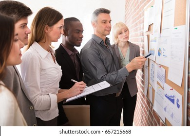 Mature Manager Analyzing The Graph With His Colleague Attached On Bulletin Board