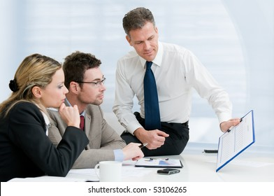 Mature manager giving a presentation to his business colleagues in modern office