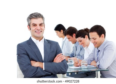Mature manager and his team writting notes in a meeting against a white background