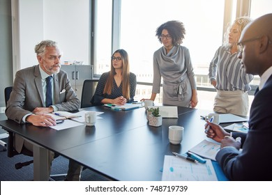 Mature manager talking to a diverse group of employees during a meeting around a table in a boardroom