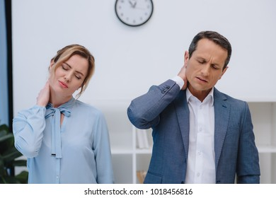 mature managers with back pain at modern office