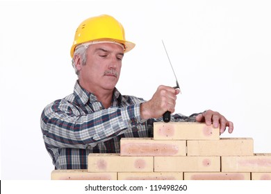 A mature mason building a wall.